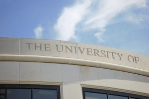 Photograph of the university of sign on top of arched office building with sky above. Windows visible below sign. Image taken on the campus of a public four year university in the United States.